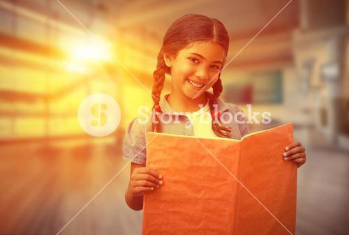 Composite image of cute pupil smiling at camera during class presentation