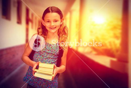 Composite image of cute little girl holding books in library