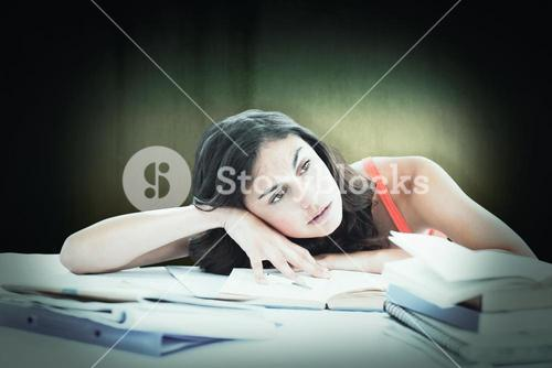 Composite image of bored female student doing her homework