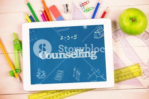 Counselling against students desk with tablet pc
