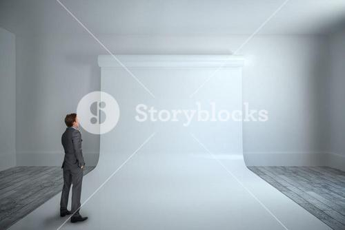 Thinking businessman against large white screen