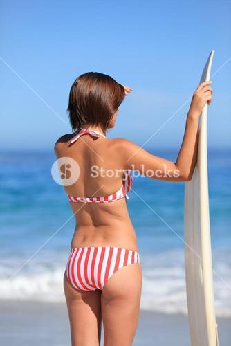 Adorable woman with her surfboard