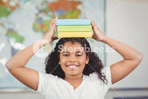 Smiling pupil balancing books on head in a classroom