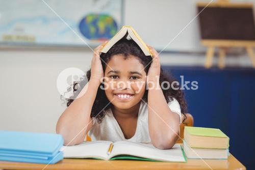 Smiling pupil holding book on head in a classroom