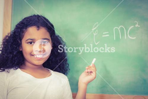 Smiling pupil standing in front of chalkboard