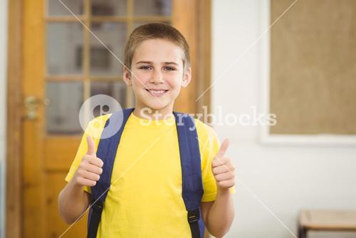 Smiling pupil with schoolbag doing thumbs up in a classroom