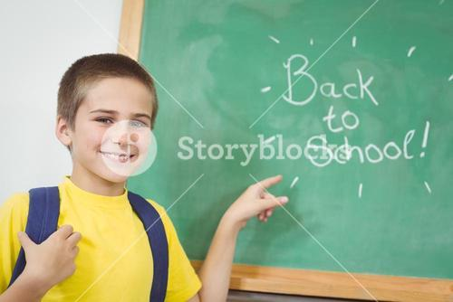 Smiling pupil pointing on back to school sign on chalkboard