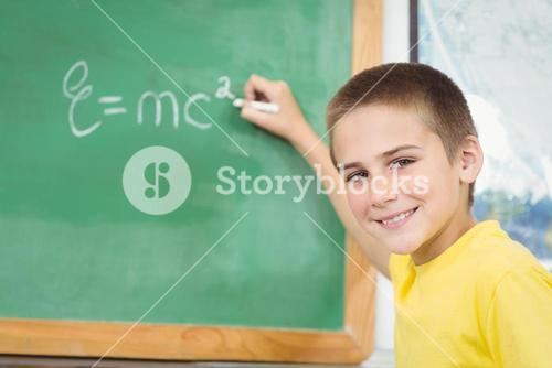 Smiling pupil writing on chalkboard in a classroom