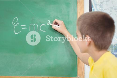 Cute pupil writing on chalkboard in a classroom