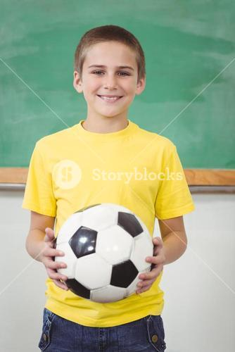 Smiling pupil holding football in a classroom