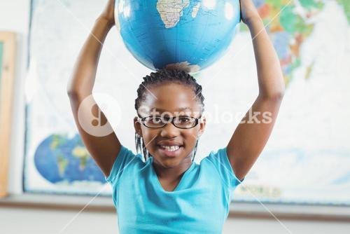 Smiling pupil holding globe in front of world map