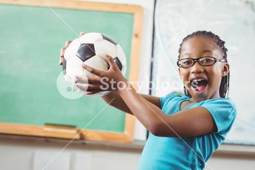 Happy pupil holding football in a classroom
