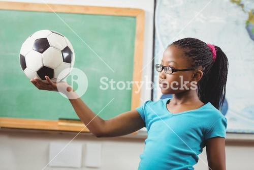 Cute pupil holding football in a classroom