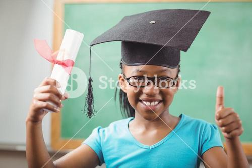 Smiling pupil with mortar board doing thumbs up