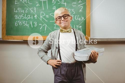 Smiling pupil dressed up as teacher holding books