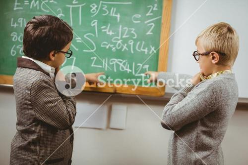 Pupils dressed up as teachers discussing in a classroom