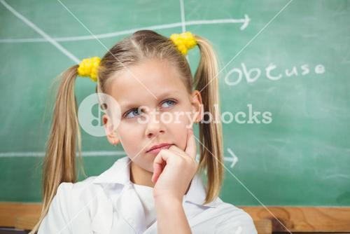 Cute pupil with lab coat thinking in front of chalkboard