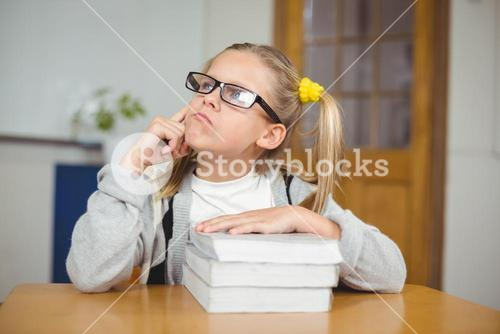 Thoughtful cute pupil sitting at her desk in a classroom