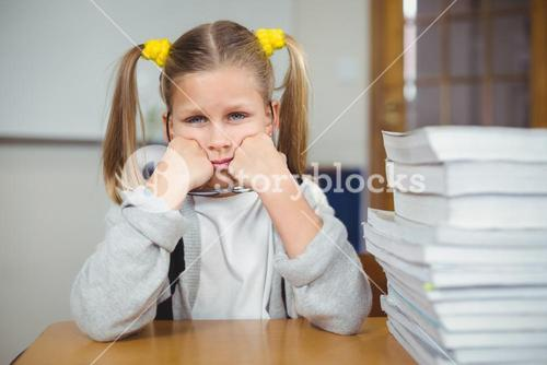 Sad pupil sitting at her desk in a classroom