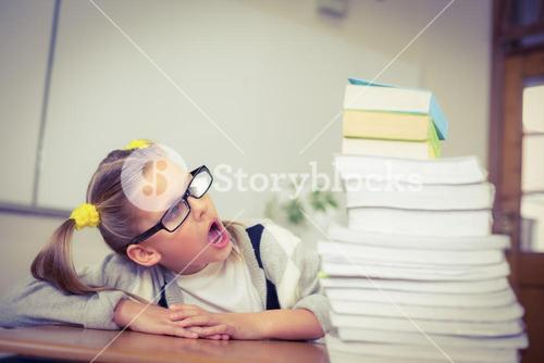 Pupil looking shocked at stack of books on her desk