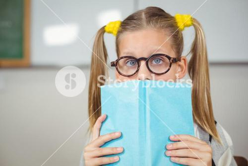 Cute pupil covering face with a book in a classroom