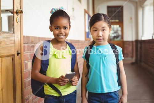 Cute pupils with smartphone at corridor
