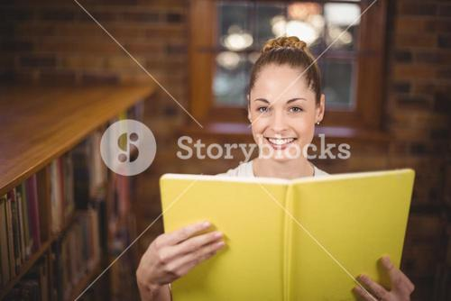 Blonde teacher reading book in the library
