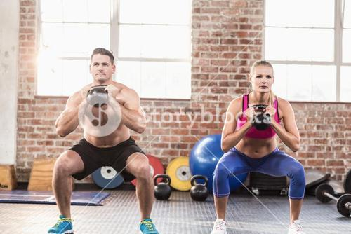 muscular serious couple with kettlebells