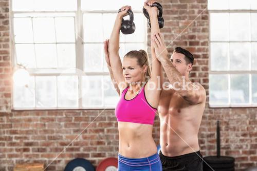 Attentive muscular trainer show how to lift kettlebells