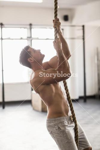 Side view of muscular man doing rope climbing