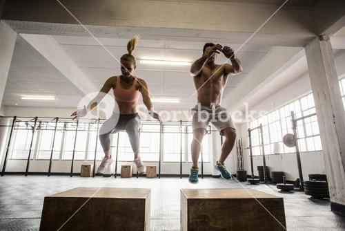 Fit couple doing set of box jumps