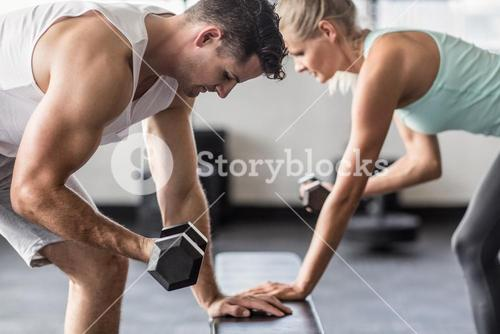 couple exercising with dumbells on a workout bench
