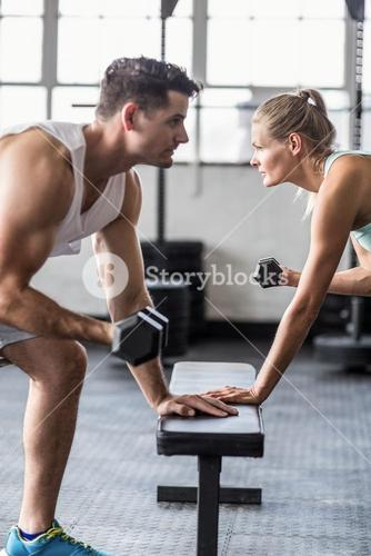 couple exercising with dumbbells in crossfit gym