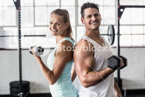 Smiling couple exercising with dumbbells
