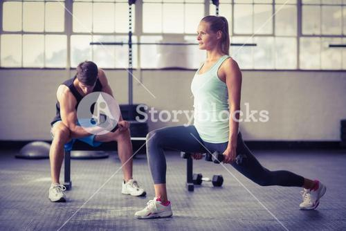 Serious couple exercising with dumbbells