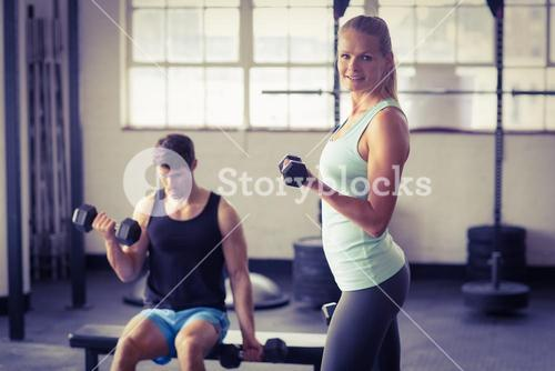 Sporty couple exercising with dumbbells