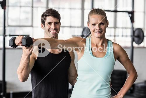 Male trainer helping woman with the dumbbells