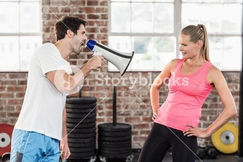 Personal trainor motivating his client with megaphone