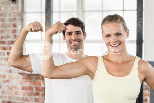 Portrait of couple flexing muscles