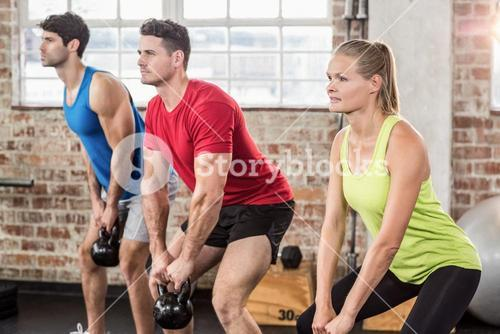Muscular people lifting a kettle bell