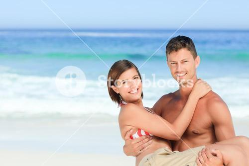 Man carrying his wife at the beach