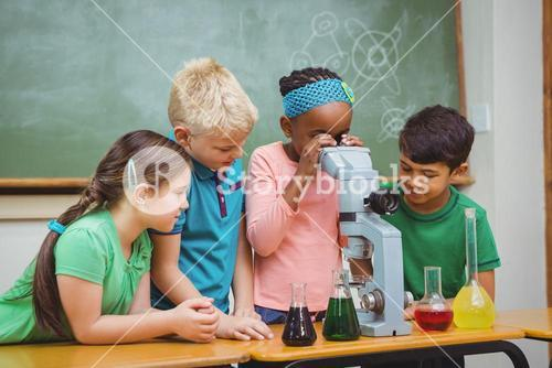 Students using science beakers and a microscope