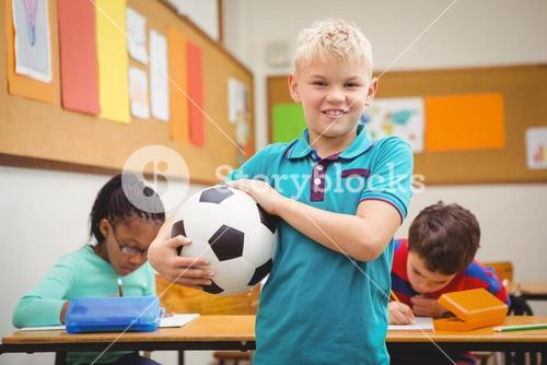 Smiling student holding a football