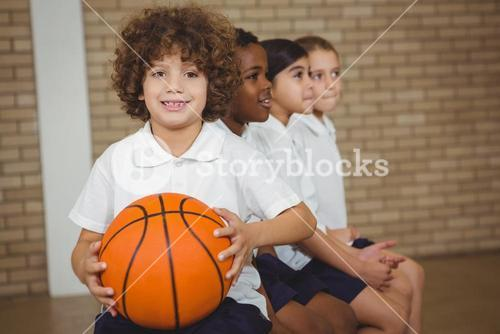 Student holding basketball with fellow players