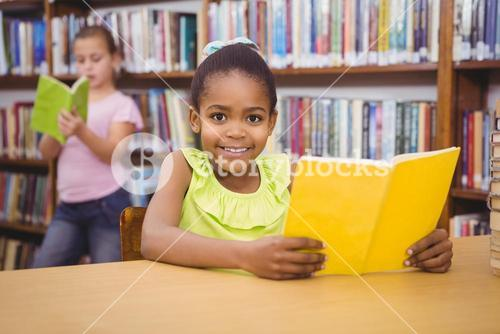 Happy pupil reading a library book