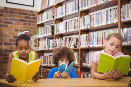 Happy pupils reading a library book