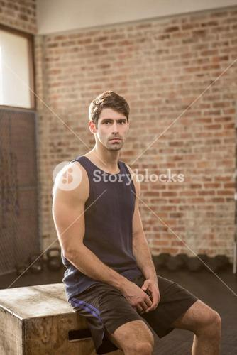 Portrait of man sitting on plyo box