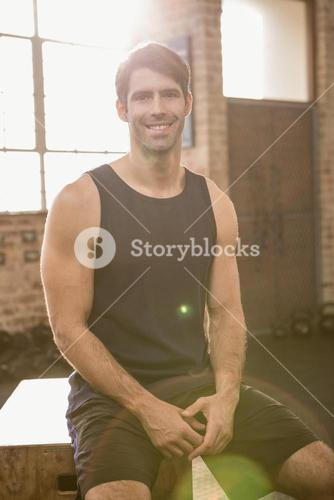 Portrait of a smiling man sitting on plyo box