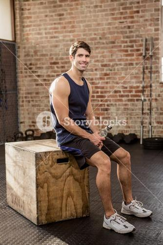 Man sitting on plyo box holding water bottle