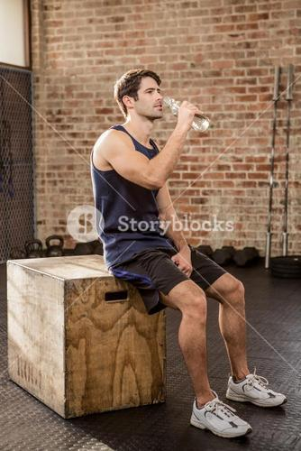 Man sitting on plyo box and drinking water